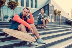 Two urban males posing with longboard. Two urban males posing with longboard on steps in downtown Stock Image