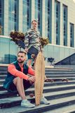 Two urban males posing with longboard. Two urban males posing with longboard on steps in downtown Stock Photo