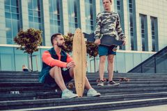 Two urban males posing with longboard. Two urban males posing with longboard on steps in downtown Royalty Free Stock Photos