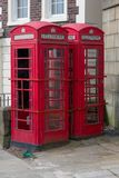 Two Urban Red Telephone Boxes. Two red telephone boxes stand abandoned and damaged in an urban setting royalty free stock image