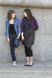 Two urban teen girls standing at wall Stock Photography