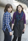 Two urban teen girls standing at wall. Royalty Free Stock Images