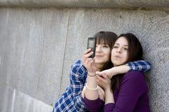 Two urban teen girls taking photo Royalty Free Stock Photos