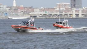 Two US Coast Guard boat drives along city coast. Two US Coast Guard boat drives along a coast. In the background is a US city stock video