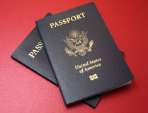 Two US Passports on Red Background. Two blue United States passports arranged on a fine textured red background material Royalty Free Stock Images