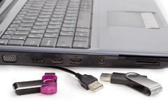 Two USB flash drives and USB cable against of laptop. Two different USB flash drives and USB cable closeup on background of a side part of laptop at shallow Stock Images