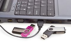 Two USB flash drives and USB cable against of laptop. USB cable connected to laptop and two different USB flash drives beside on a background of a side part of Stock Photos