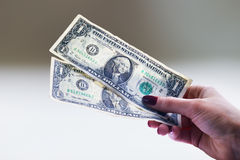 Two used one dollar banknotes in a woman's hand Stock Photos