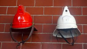Fireman Helmets. Two used red and white older  helmets similar as the first roman helmts used by firemen, equipment used by firemen made of fiber glass Stock Photo
