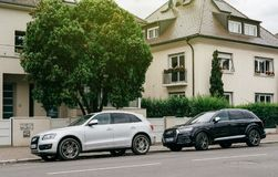 Two uxury Audi cars parked in front of house. PARIS, FRANCE - JUN 25, 2017: Two luxury allroad Audi vehicles parked in an upper-class neighbourhood in Strasbourg royalty free stock photography