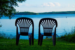 Two vacant places. Available, empty chairs by a lake Stock Photos
