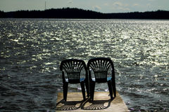 Two vacant places. Available, empty chairs by a lake Stock Photography