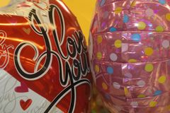 Two Valentine balloons - one red and white that says I Love You and one pink polka dot - closeup stock images