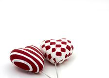 Two valentine hearts. A small heart with stripes and one with squares Royalty Free Stock Photos