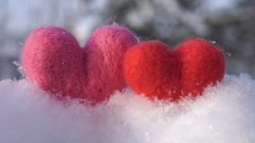 Two Valentine`s woolen hearts on the clear white snow in winter slow motion. Valentine`s day concept two toy hearts made of red and pink wool standing on the stock video