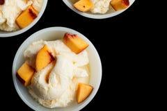 Two vanilla ice-cream with peach  on black. Royalty Free Stock Photo