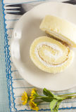 Two vanilla roll cake on the blue stripe clothes. The vanilla roll cake on the blue stipes clothes,yellow small flower on blue pale background Royalty Free Stock Photos