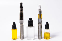 Two Vape E-Cig and Three vape juice bottles Royalty Free Stock Photos