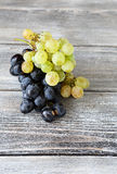 Two varieties of Sweet grapes on wooden background Royalty Free Stock Image