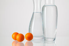Two vases with clean water and golf balls Royalty Free Stock Photos