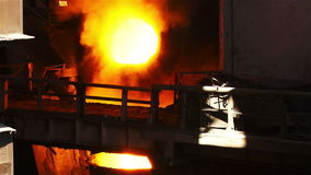 Two vat of liquid metal and fire shoots up. Molten metal melted in furnace at metallurgical plant stock video footage