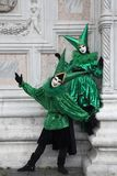 2 Venetian Carnival Figures in a colorful green and black costumes and masks Venice Italy Stock Images