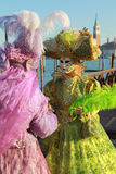 Two venetian mask in pink and green dress Stock Photos