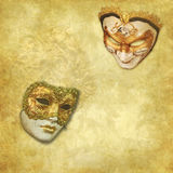 Two Venetian masks on a rich golden background. Two Venatian masks on a vintage golden background with fading effects stock illustration
