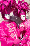 Two Venetians in pink costumes. On a sunny day Royalty Free Stock Photos