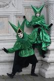 Two Venice Carnival costumes in green and black with Venice masks in February`s Venice Carnival Italy royalty free stock photo