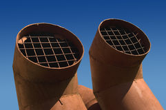 Two ventilation pipes. Two periscope shaped ventilation pipes against a blue sky. Clipping path included stock photography
