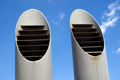 Two ventilation pipes over blue sky closeup Stock Photo