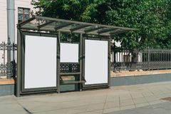 Two vertical blank white billboards at bus stop on city street. In the background buildings and trees. Mock up. royalty free stock image