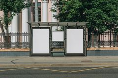 Two vertical blank white billboards at bus stop on city street. In the background buildings and trees. Mock up. stock image