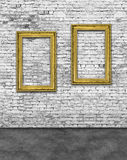 Two vertical golden frames on brick wall. Two vertical golden frames on white brick wall Stock Photography