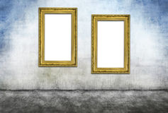 Two vertical golden frames. On gray dirty wall Stock Image