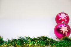 Two vertical,pink christmas balls and Christmas decoration on a white background. Festive, Christmas card,two vertical pink balls, and Christmas decorations on a Stock Photo