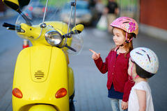 Two very curious little girls and a motorcycle Royalty Free Stock Photography