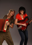 Two very funny music girls. Two girls playing musical instruments and smiling Royalty Free Stock Images
