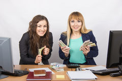 Two very happy office girl happily holding wads of money in their hands and look in the frame Royalty Free Stock Photos