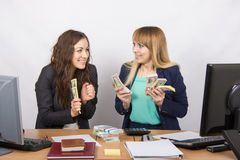 Two very happy office girl happily holding wads of money in their hands Stock Images