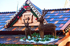 Two, very nicely done deer standing on a roof with colored tiles. Christmas market. Snow and green branches of the spruce. Soon Christmas and New Year Royalty Free Stock Photos