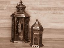 Two very old silver lanterns on bleached oak background. Sepia colour. Rustic, retro style. Two old lanterns made of silver and colourful glass. Handicrafts royalty free stock photography