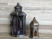 Two very old silver lanterns on bleached oak background. Rustic, retro style. Two old lanterns made of white tinn metal silver and colourful glass. Handicrafts stock photography