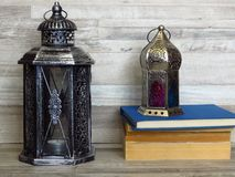 Two very old silver lanterns and a pile of old books on bleached oak background. Two very old silver lanterns and a pile of very old books on bleached oak stock images