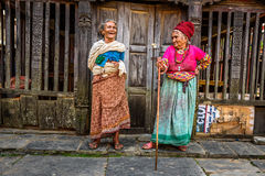 Two very old women discuss in Bandipur, Nepal. BANDIPUR, NEPAL - OCTOBER 22, 2015 : Two very old women discuss in the street of Bandipur in Nepal Royalty Free Stock Image