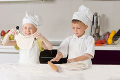 Two Very Young Chefs Flatting Pizza Dough Stock Photo