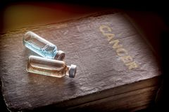 Two vials on a book of cancer royalty free stock photo