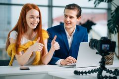 Two video bloggers showing thumbs up and smile Stock Images