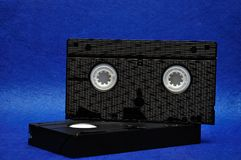 Two video cassettes. Isolated on a blue background stock photos